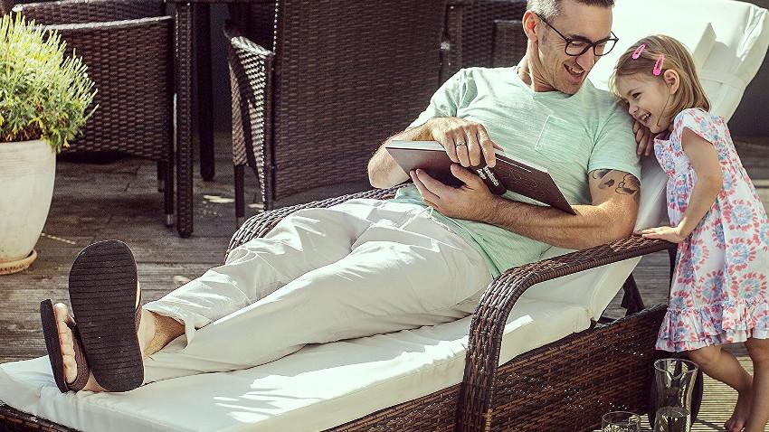 Ein Mann liegt auf einer grauen Sonnenliege und liest ein Buch. Daneben steht ein kleines Mädchen