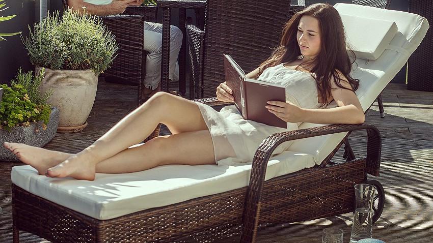 Frau liegt auf großer Sonnenliege aus Rattan und liest ein Buch. Die Liege steht im Garten